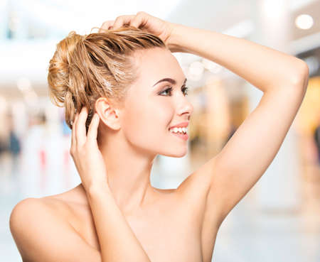 Photo for Portrait of a smiling young woman washing her hair - Royalty Free Image