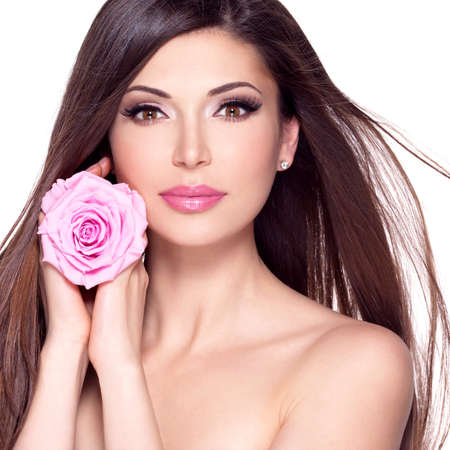 Photo for Portrait of a beautiful white pretty woman with long straight hair and pink rose at face. - Royalty Free Image