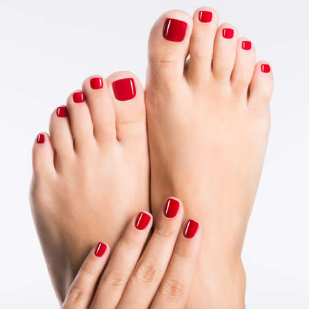 Closeup photo of a female feet with beautiful red pedicure over white backgroundの写真素材