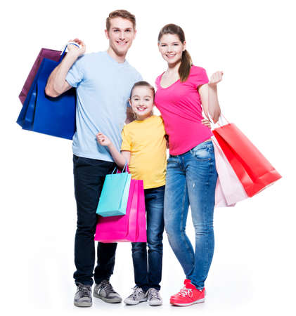 Foto de Happy family with shopping bags standing at studio over white background. - Imagen libre de derechos