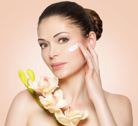 Photo for Young woman with cosmetic  cream on a clean fresh face. Healthy lifestyle concept - Royalty Free Image