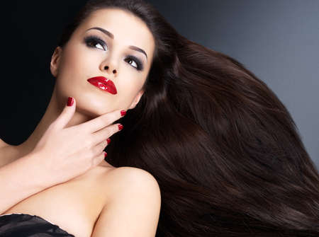 Photo pour Beautiful woman with long brown straight hairs and red nails lying on the dark background - image libre de droit