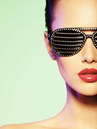 Photo pour Fashion portrait of  woman wearing black sunglasses with diamonds. Saturated colors - image libre de droit