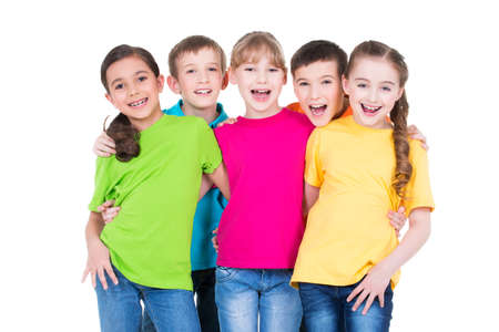 Foto de Group of happy children in colorful t-shirts standing together on white background. - Imagen libre de derechos