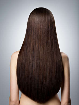 Foto de Rear Portrait of  woman with long brown straight  hair at studio - Imagen libre de derechos