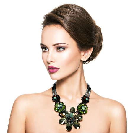 Foto de Beautiful woman with fashionable jewelry.  Portrait of a pretty fashion girl with green glass necklace. American Model posing over white background - Imagen libre de derechos