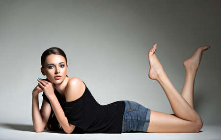 Beautiful woman in black t-shirt and blue jeans shorts. Fashion young girl with long legs posing at studio