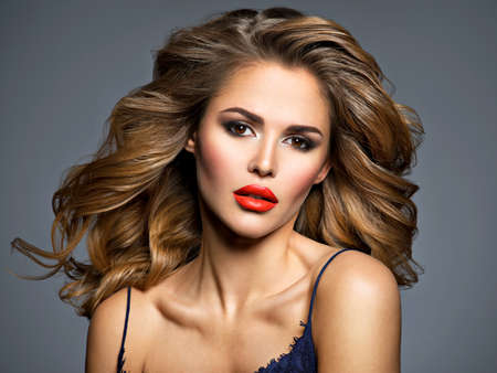 Beautiful young woman with long brown hair. Closeup portrait with a pretty female face. Fashion model with red lips.