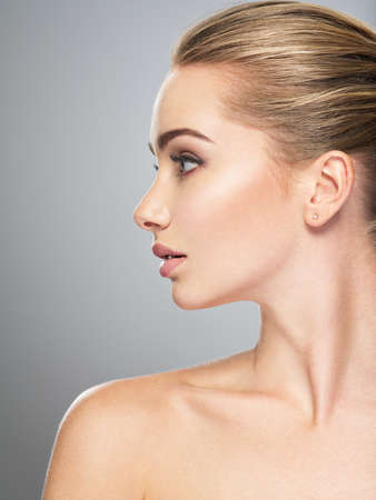 Foto de Profile face of  young  woman, skin care treatment. Side view of beautiful girl with healthy skin of the face - Imagen libre de derechos