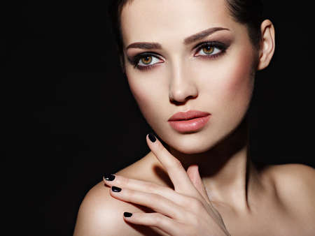 Photo pour Face of a beautiful girl with fashion makeup and black nails posing at studio over dark background - image libre de droit