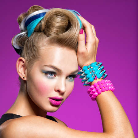 Photo pour Fashion portrait of young caucasian model with bright makeup. Beautiful woman with creative hairstyle. woman with  Fashion make-up. Closeup portrait. Gorgeous face of an attractive girl - pink background. Portrait of a girl with bracelets on her hands in the form of thorns. Jewelry - image libre de droit