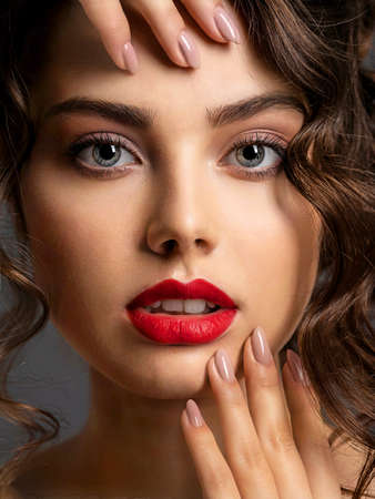 Photo pour Closeup Face of a beautiful woman with a smoky eye makeup and red lipstick. Sexy brunette girl  with long curly hair. Portrait of an attractive female -  at studio. Fashion model. Beautiful eyes. - image libre de droit