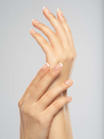 Photo pour Woman gets manicure procedure in a spa salon. Beautiful female hands. Hand care. Woman cares for the nails on hands. Beauty treatment with skin of hand.   Woman's hands close-up view. - image libre de droit