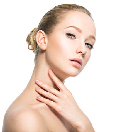 Photo pour Beautiful face of young caucasian woman with perfect health skin  - isolated on white.  Skin care concept. Female touches the neck - image libre de droit