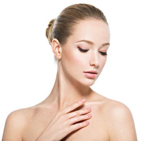 Photo pour Beautiful face of young caucasian woman with perfect health skin  - isolated on white.  Skin care concept. Female Model touches face. - image libre de droit