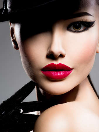 Photo for Ð¡lose-up portrait of a woman in a black hat and gloves with red lips posing at studio - Royalty Free Image