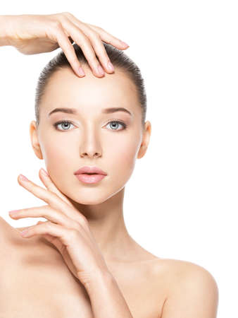 Photo pour Young woman with healthy clean skin touches the face - isolated on white.  Skin care concept. - image libre de droit