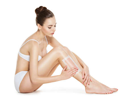 Photo pour beautiful young woman depilating her legs by waxing -  studio on white background - image libre de droit