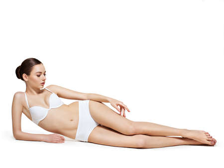 Photo pour Beautiful woman with perfect body lying on white background - image libre de droit