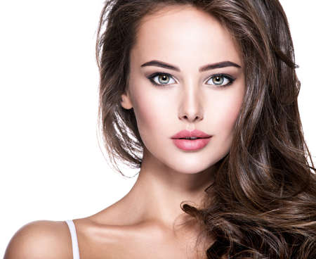 Photo pour Attractive face of beautiful young  woman with long brown curly hair. Fashion model poses at studio. - image libre de droit