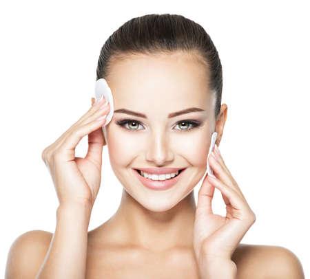 Photo pour Beautiful woman cleans the face with cosmetic cotton swab. - image libre de droit