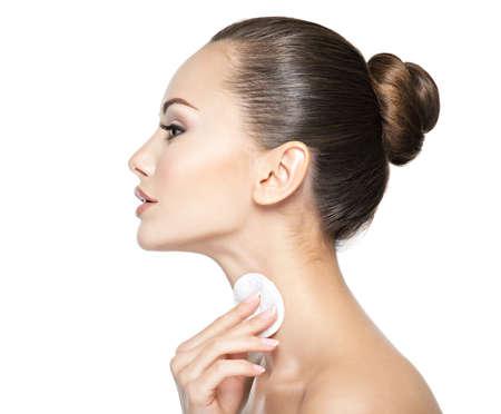 Photo pour Beautiful woman cleans the neck with cosmetic cotton swab. - image libre de droit