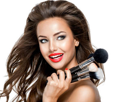 Photo pour Beautiful happy expressive young woman holds the makeup brushes and looking away - image libre de droit