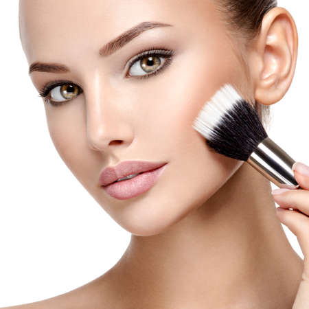 Photo for Portrait of a woman  applying cosmetic makeup on the face using makeup brush. - Royalty Free Image