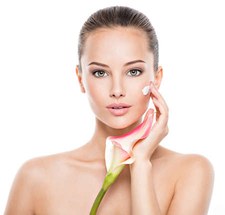 Photo pour Woman applying cosmetic  cream on a face. Fresh flower on the body - image libre de droit