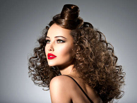 Photo pour Beautiful woman with creative hairstyle. Attractive portrait of the fashion model with curly hair. - image libre de droit