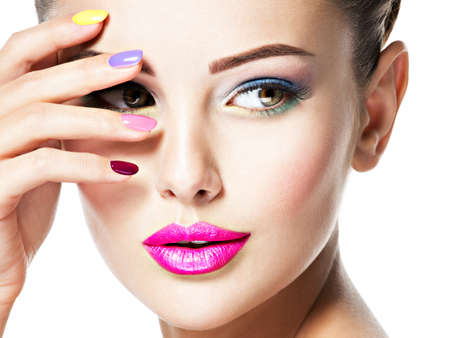 Photo for Close-up face of a beautiful woman  with multicolor nails and fashion makeup . - Royalty Free Image