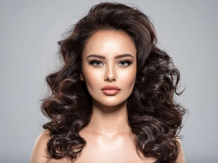 Photo pour Beautiful woman with brown hair. Beautiful face of an attractive model with beige makeup. Portrait of a beautiful woman with a long hair.  Fashion model. Beautiful stunning girl  with a  curly hairstyle. - image libre de droit