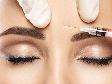 Photo pour Portrait of young Caucasian woman getting botox cosmetic injection in forehead. Beautiful woman gets botox injection in her face. - image libre de droit