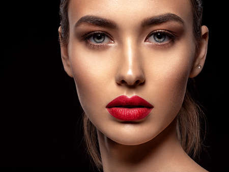 Photo pour Beautiful young fashion woman with red lipstick. Glamour fashion model with bright gloss make-up  posing at studio. Closeup beauty portrait. - image libre de droit