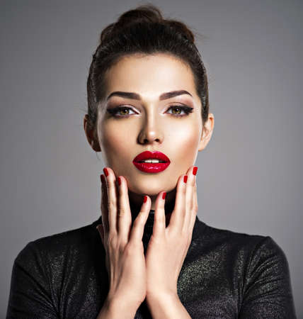 Foto de Closeup portrait of beautiful woman with bright make-up and red nails. Sexy young adult girl with red lipstick. - Imagen libre de derechos