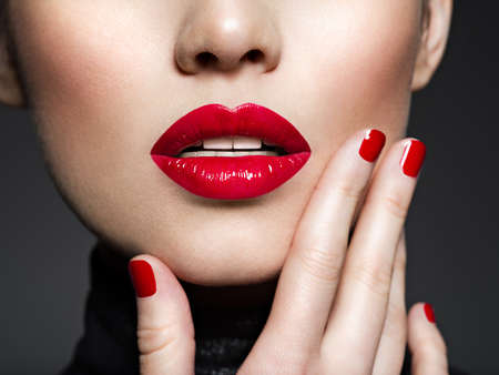 Photo pour Closeup sexy female lips with red lipstick. Glamour fashion bright gloss make-up and manicure. - image libre de droit