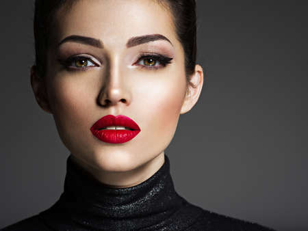Photo pour Beautiful young fashion woman with red lipstick. Glamour fashion model with bright gloss make-up  posing at studio. - image libre de droit