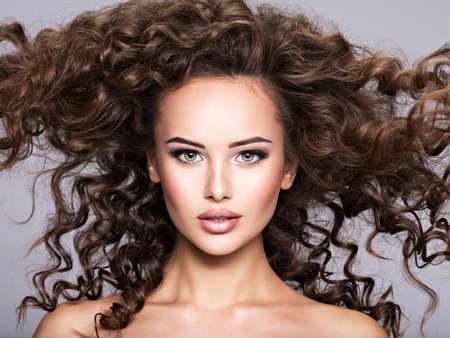Photo for woman with long bown curly hair. Portrait of a Beautiful Brunette sexy girl with long hair - Royalty Free Image