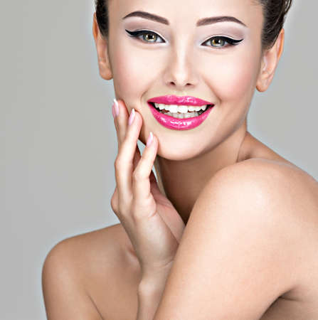 Photo pour Smiling happy face of a pretty young woman  with creative hairstyle .  Studio photo. - image libre de droit