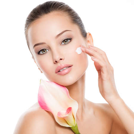 Foto de Woman applying cosmetic  cream on a face. Fresh flower on the body - Imagen libre de derechos