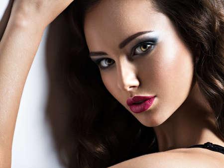 Foto de Face of the beautiful woman with long brown curly hair posing at studio over dark background - Imagen libre de derechos