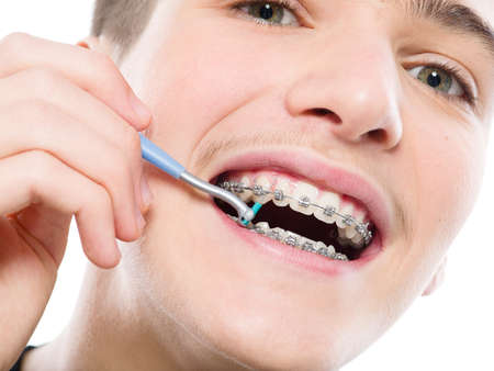 Photo pour Photo of a guy  cleaning braces.  Young man taking care of his teeth. Dental hygiene. Teenager brushes braces, isolated on white. - image libre de droit
