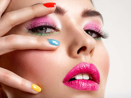 Photo pour Beautiful fashion woman with a colored nails. Attractive white girl with multicolor manicure. Glamour fashion model with bright gloss make-up posing at studio. Stylish fashionable concept. Art - image libre de droit