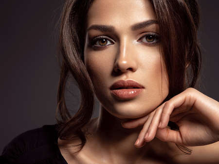 Photo for Beautiful woman with brown hair. Attractive model with brown eyes. Fashion model with a smokey makeup. Closeup portrait of a pretty woman looks at camera. Sexy woman. - Royalty Free Image