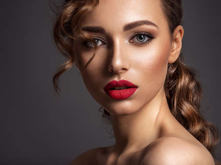 Photo pour Beautiful face of young woman with red lipstick. Portrait of a stunning sexy girl looks at camera. Attractive model with stylish makeup.  Closeup portrait of a caucasian female. - image libre de droit
