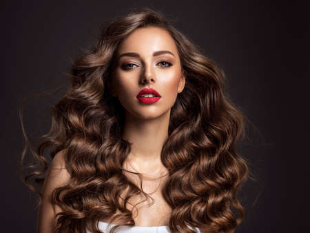 Photo pour Beautiful woman with long brown hair. Beautiful face of an attractive model with red lipstick. Beauty  of curly hair. Closeup portrait  of caucasian stunning girl. - image libre de droit