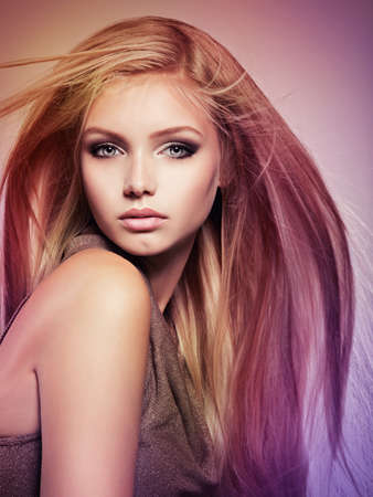 Photo pour Face of the Beautiful young woman with long straight  hair.  Closeup portrait of a attractive girl over creative colored background - image libre de droit