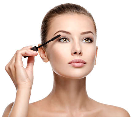 Photo pour woman applying cosmetic mascara on eyelashes using curling brush - isolated on white - image libre de droit