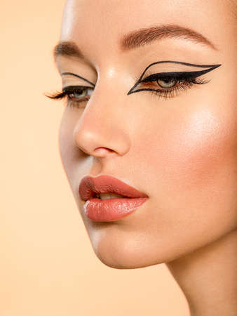 Photo pour Beautiful girl with makeup in the form of arrows. Face of a young girl close-up with fashionable makeup over beige background. Stylish makeup. - image libre de droit