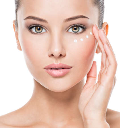 Photo pour Portrait of woman with healthy face applying cosmetic cream under the eyes - image libre de droit